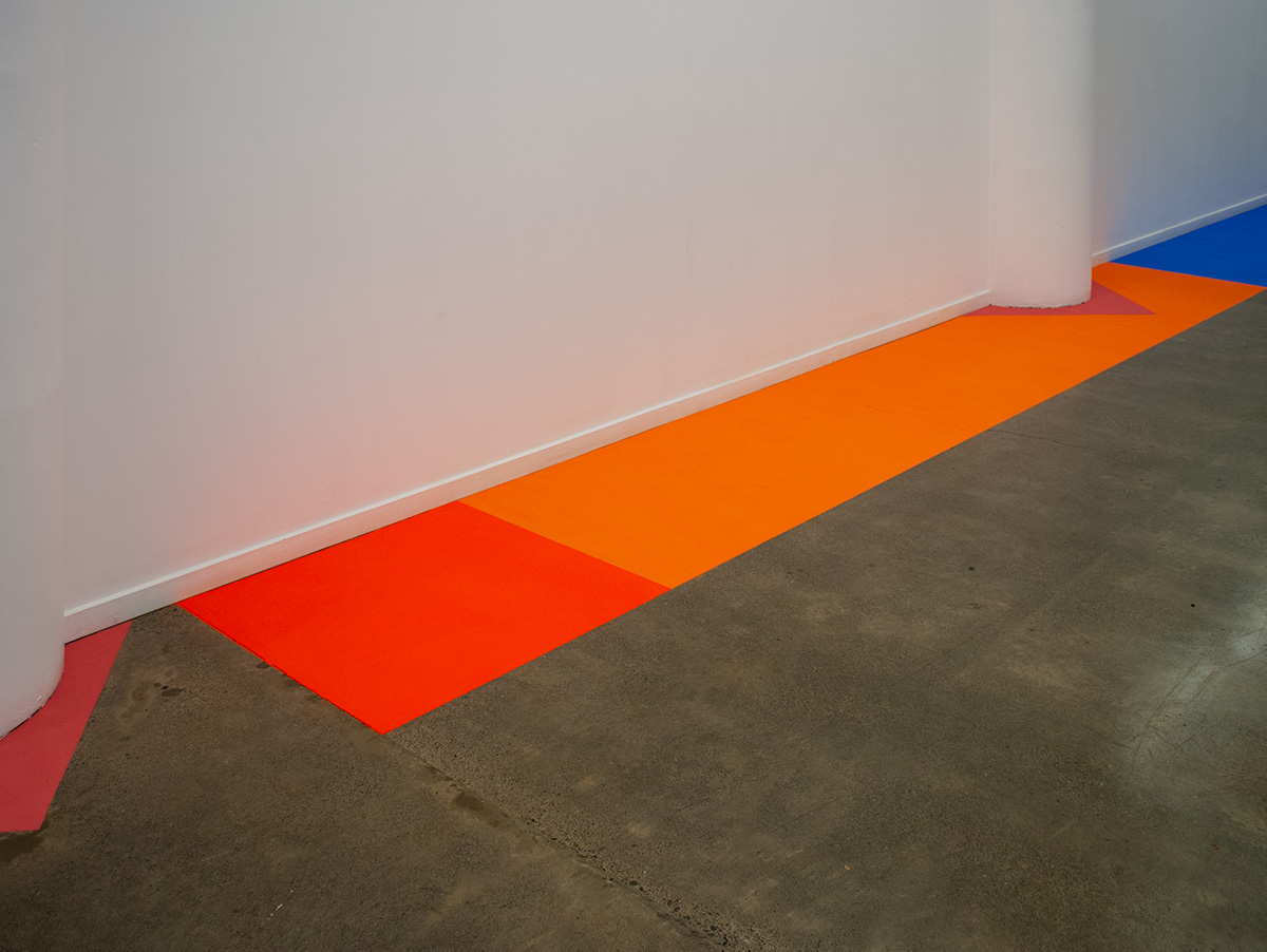A short fluorescent orange rectangle, butts up to a long orange rectangle which in followed by a mid sized blue powder paint rectangle. All run along the edge of the wall.