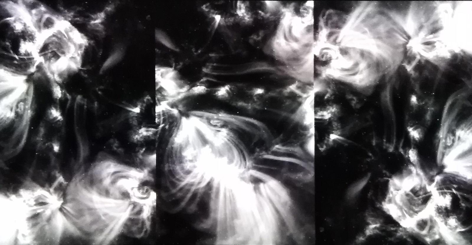 A three panel blakc and white abstract video image of swirling forces.